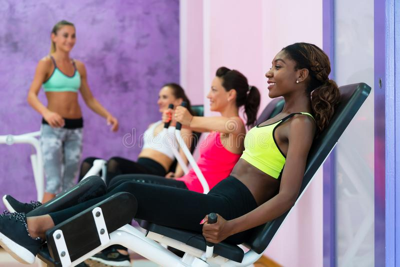 Young woman doing exercise for legs while attending group class. Happy young women with a healthy lifestyle doing exercise for toned legs while attending group stock photos