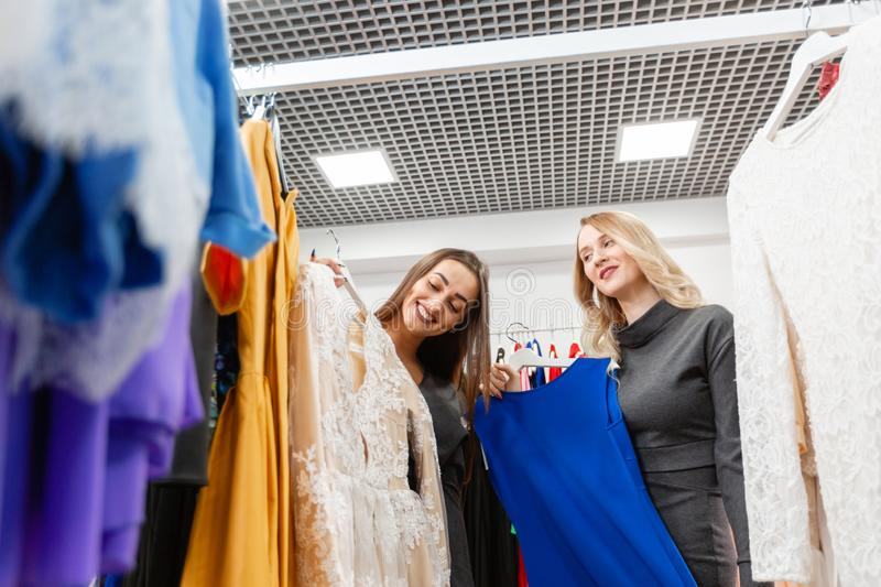 Happy young woman choosing clothes in mall or clothing store royalty free stock photography