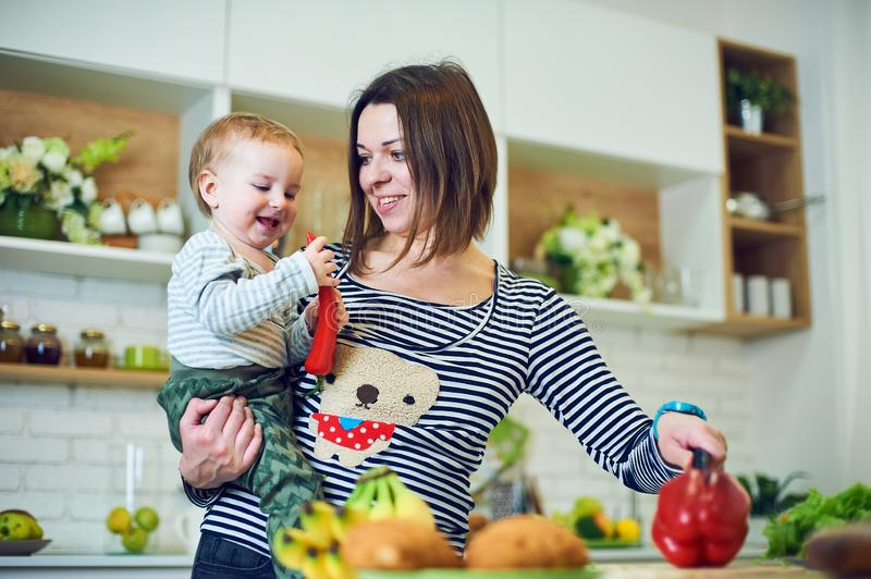 Happy young woman holding a 1 year old child and cooking together in the kitchen stock images