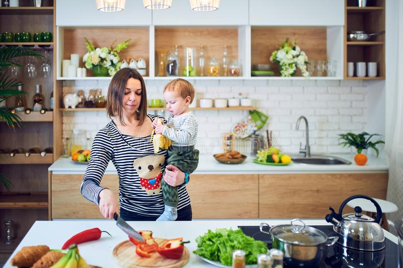Happy young woman holding a 1 year old child and cooking together in the kitchen stock image
