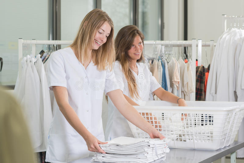 Happy young women laundry workers at dry cleaners royalty free stock photo