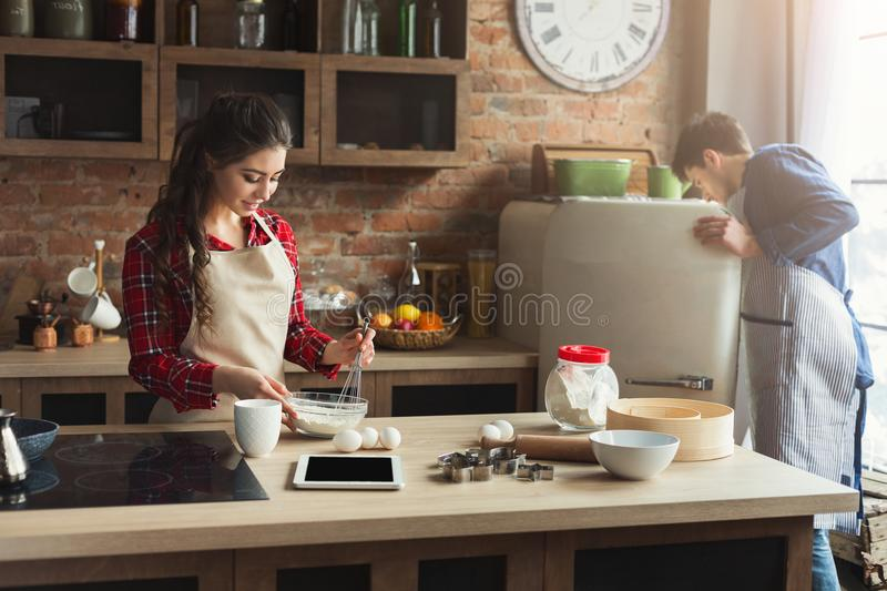 Happy young couple baking in loft kitchen royalty free stock photos
