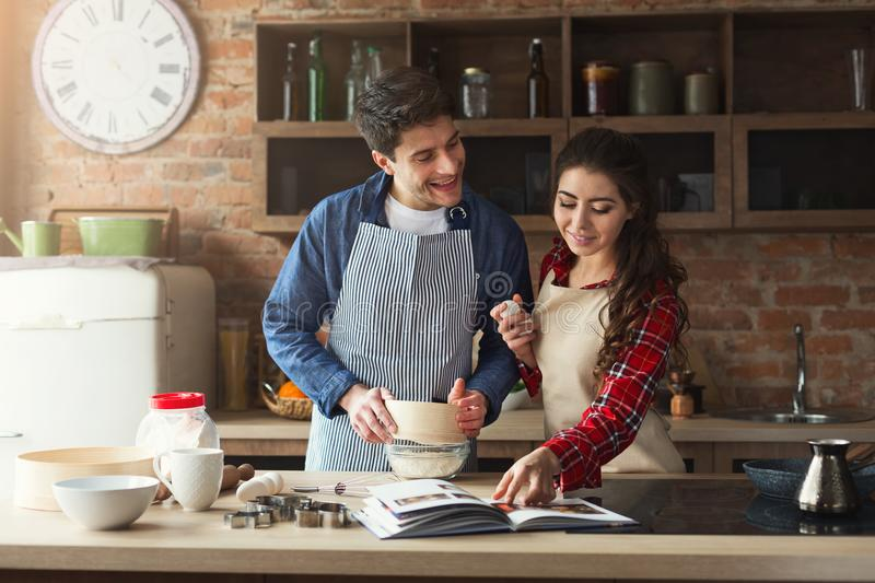 Happy young woman and man baking in loft kitchen royalty free stock photography