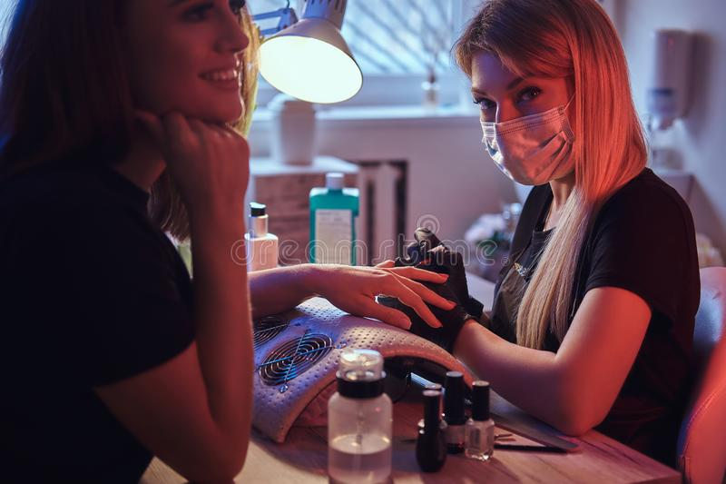 Happy young woman receiving a manicure by a beautician master in the beauty salon. royalty free stock images