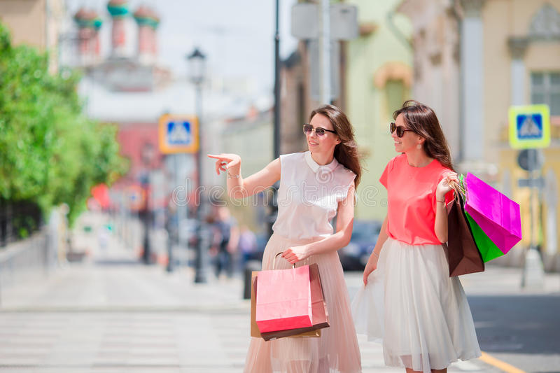 Happy young women with shopping bags enjoy their day walking along city street. Sale, consumerism and people concept. royalty free stock photography
