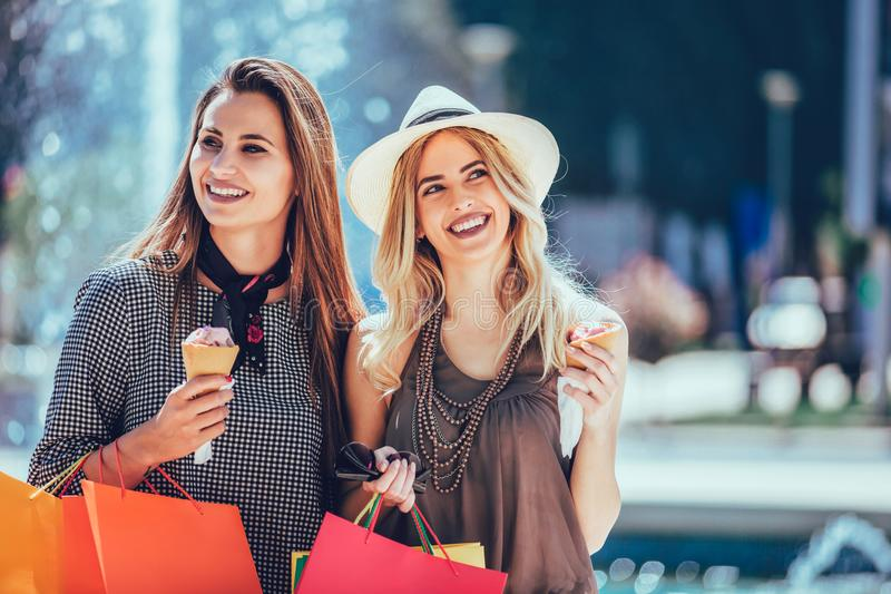 Young women with shopping bags and ice cream having fun stock photography