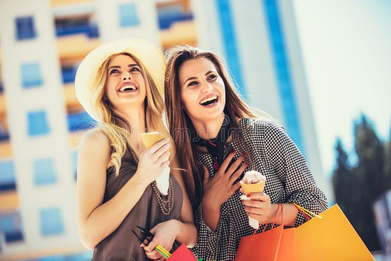 Young women with shopping bags and ice cream having fun stock photo