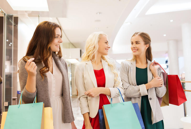 Happy young women with shopping bags in mall. Sale, consumerism and people concept - happy young women with shopping bags talking in mall stock images