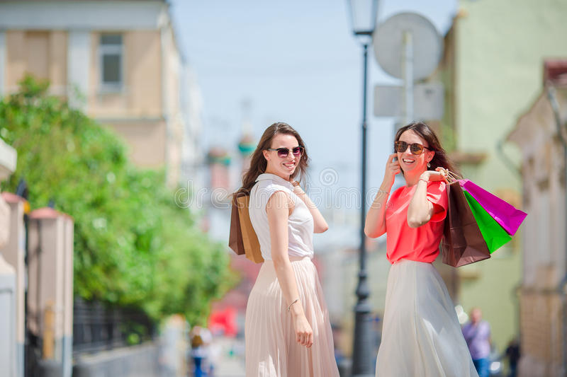 Happy young women with shopping bags walking along city street. Sale, consumerism and people concept. stock photography