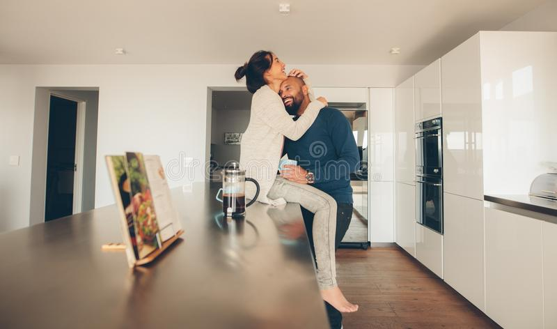 Loving young couple in morning in kitchen stock photos