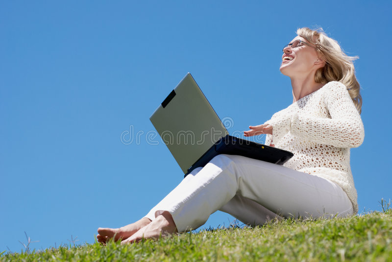 Happy young woman smiling and working on a laptop stock image