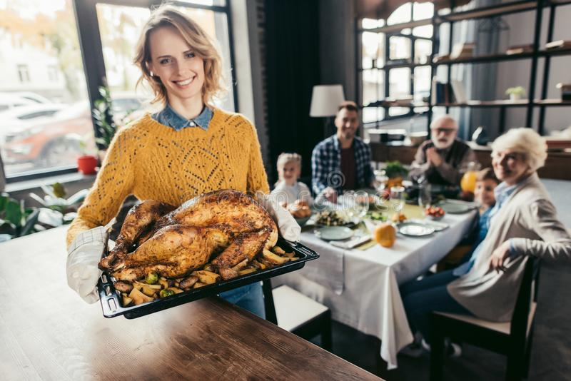 Happy young woman with thanksgiving turkey for holiday dinner with family and looking. Happy young women with thanksgiving turkey for holiday dinner with family royalty free stock photos
