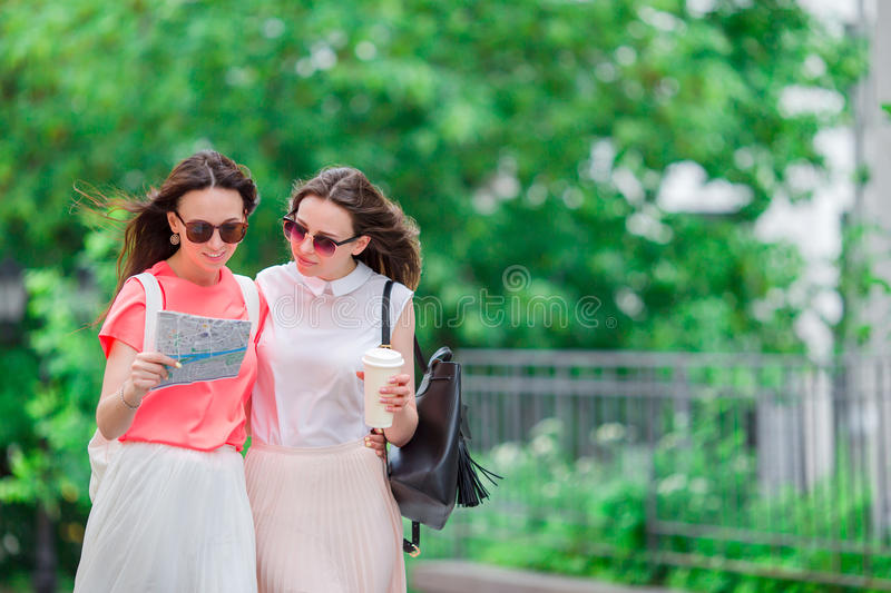 Happy young women with touristic map walking along city street. stock images