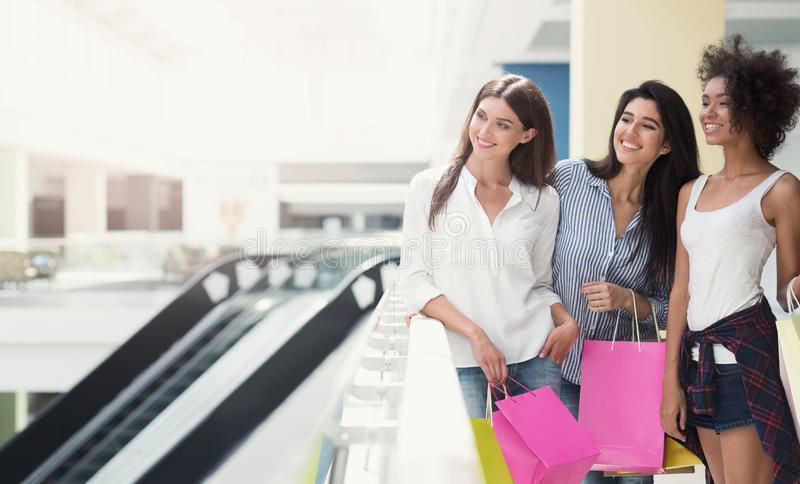 Happy women walking in mall with shopping bags stock photography