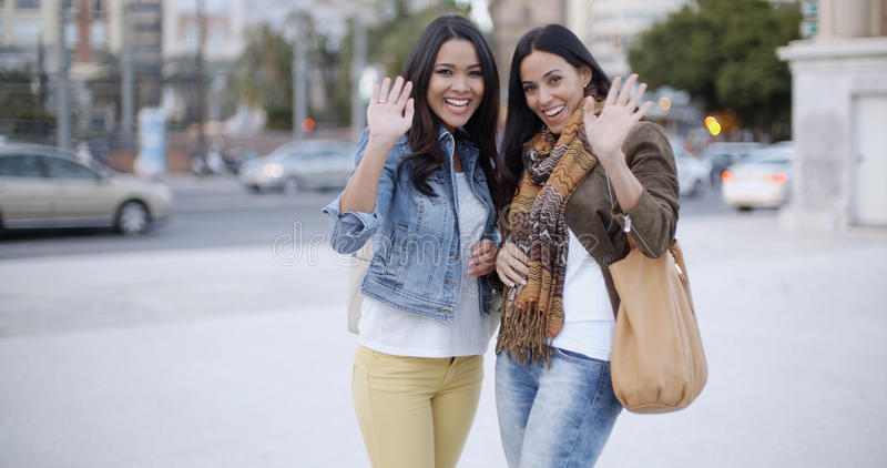 Happy young women waving at the camera royalty free stock photos