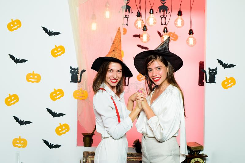 Happy young women in witch halloween costumes on party over isolated background. Halloween dresses and witch costumes. Design. Best ideas for Halloween. Spooky royalty free stock image