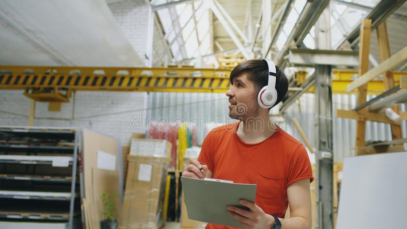 Happy young worker in industrial warehouse listening to music and dancing during work. Man in headphones have fun at. Happy young worker in industrial warehouse stock image
