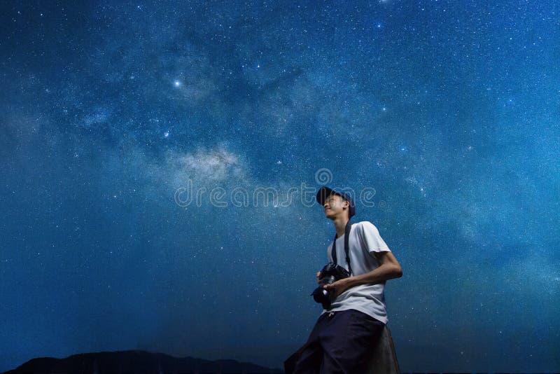 Happy Youth-fotograaf die een camera vasthoudt terwijl hij naar de lucht kijkt stock afbeelding