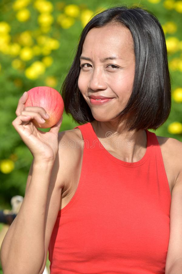 Happy Youthful Female With An Apple. An attractive and asian person royalty free stock photo