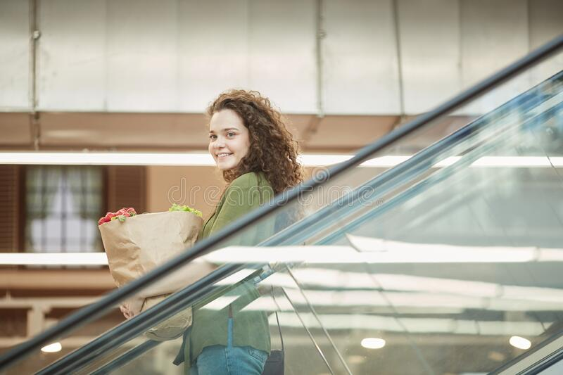 Happy Ypung Woman Holding Grocery Bag on Escalator stock photo