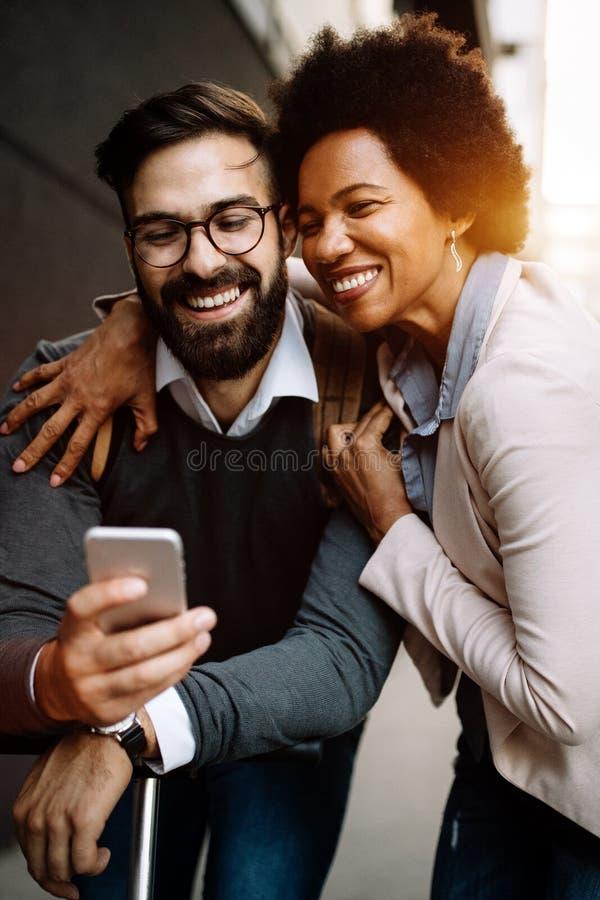 Happy-zakenmensen die gebruik maken van technologie-apparaten die gadgets nabij de muur van het moderne gebouw gebruiken stock afbeelding