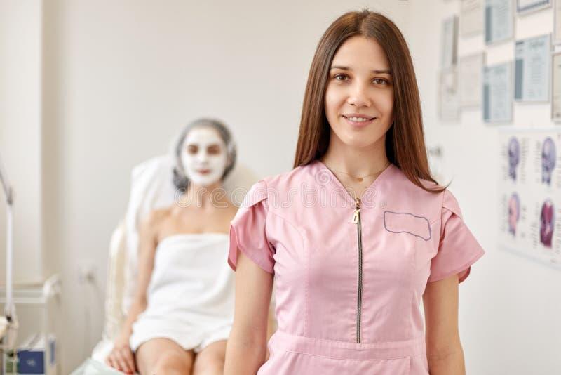 Happy zufriedener Klient liegt auf der Couch mit Cremmaske auf dem Gesicht, Kosmetikerin steht vor der Frau in rosy medizinischem lizenzfreie stockfotografie