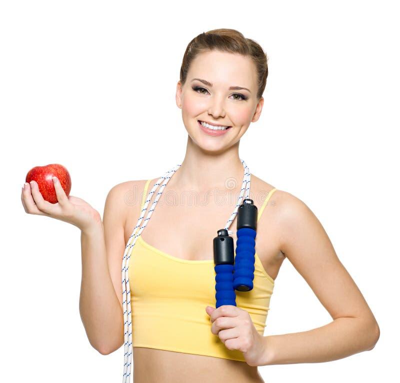Happywoman avec la pomme rouge et la corde à sauter photo stock
