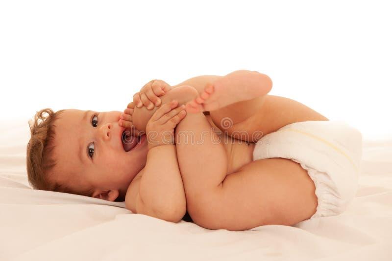 Hapy使用的男婴在床上被隔绝在白色 免版税图库摄影