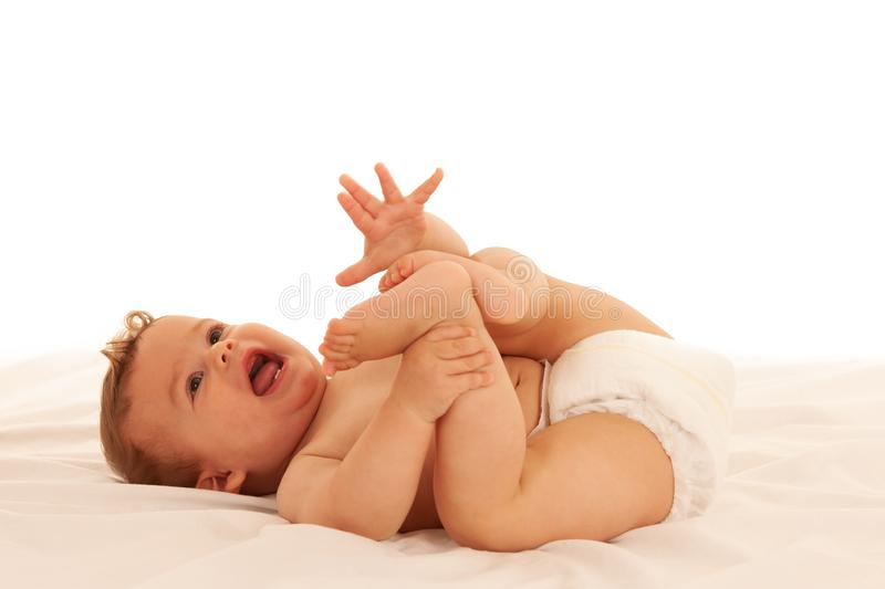 Hapy baby boy in playing on bed isolated over white stock photo