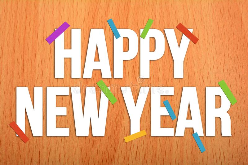 Hapy New Year on Wooden Background with colorful papers royalty free stock photo