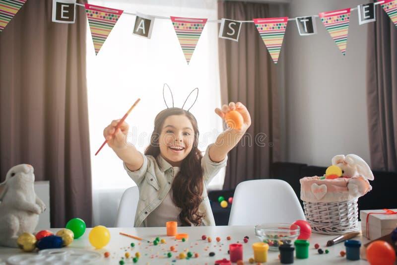 Hapy positiv flicka att förbereda sig för påsk bara Hon sitter på tabellen i rum- och målningägg Flickahållborste och ägg leende fotografering för bildbyråer