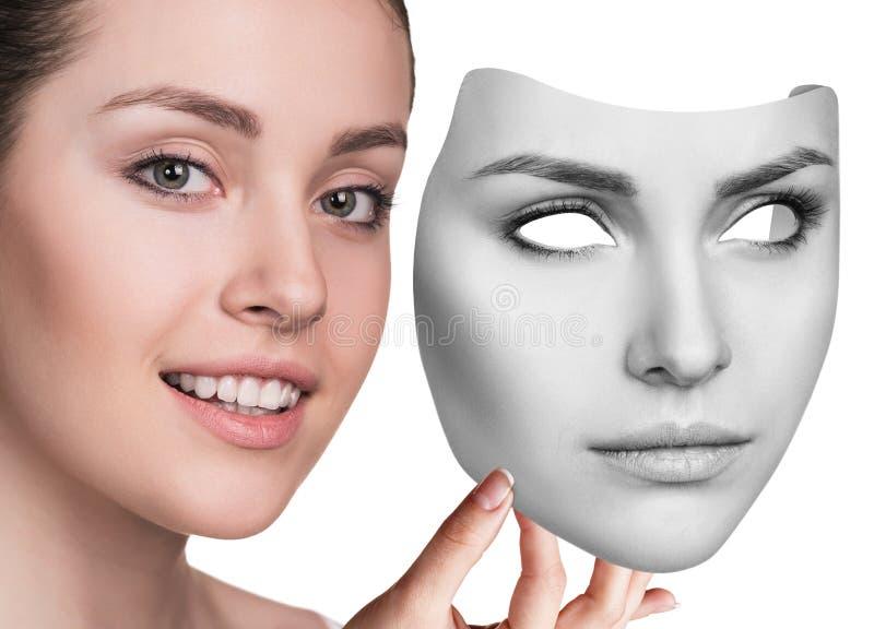 Hapyiness женщины пряча под серьезной маской стоковые фото
