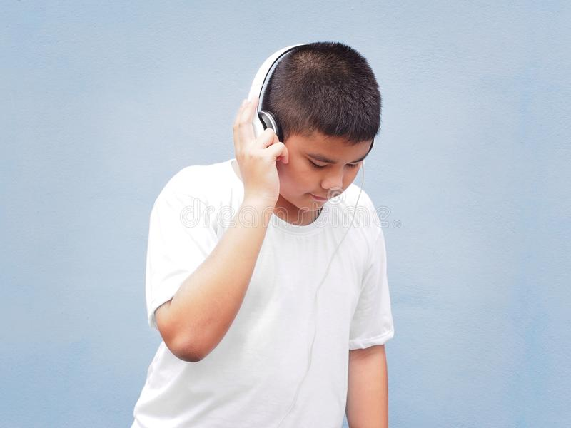 Happy asian boy with white shirt wearing headphone and listening to music over blue wall background. royalty free stock image