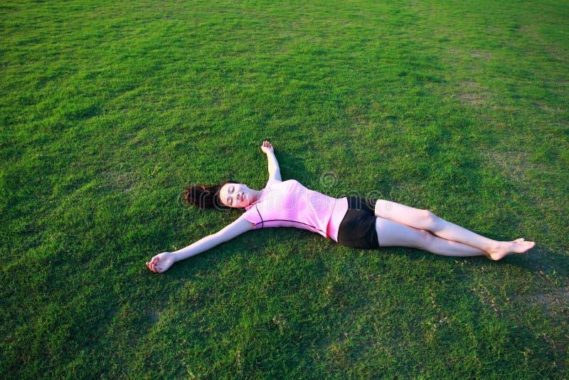 Har den asiatiska kinesiska kvinnan för kondition en vila på gräs i en parkera arkivbilder