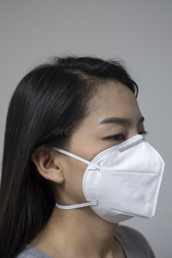 Har den bärande framsidamaskeringen för kvinnan av N95 på grund av luftförorening i staden som består av partiklar frågor eller e arkivfoto