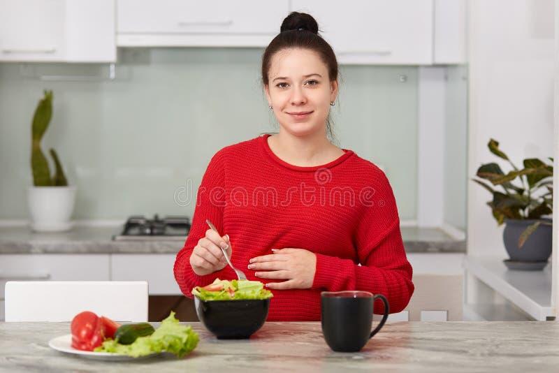 Har den framtida modern för brunetten sund lunch, äter sallad för den nya grönsaken, dricker te, sitter på modernt kök, håller ha fotografering för bildbyråer