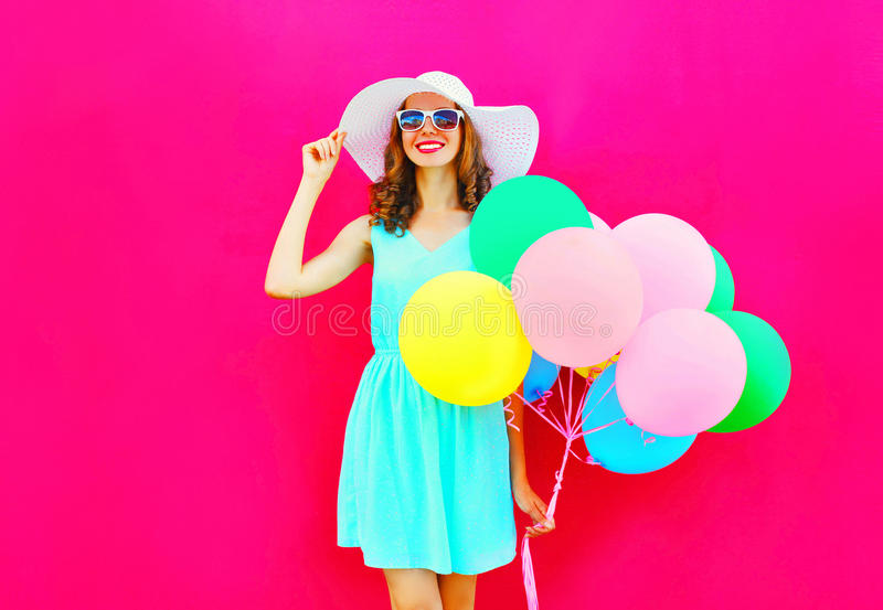 Har den lyckliga nätta le kvinnan för mode med färgrika ballonger för en luft gyckel som bär en sommarsugrörhatt över en rosa bak arkivfoto