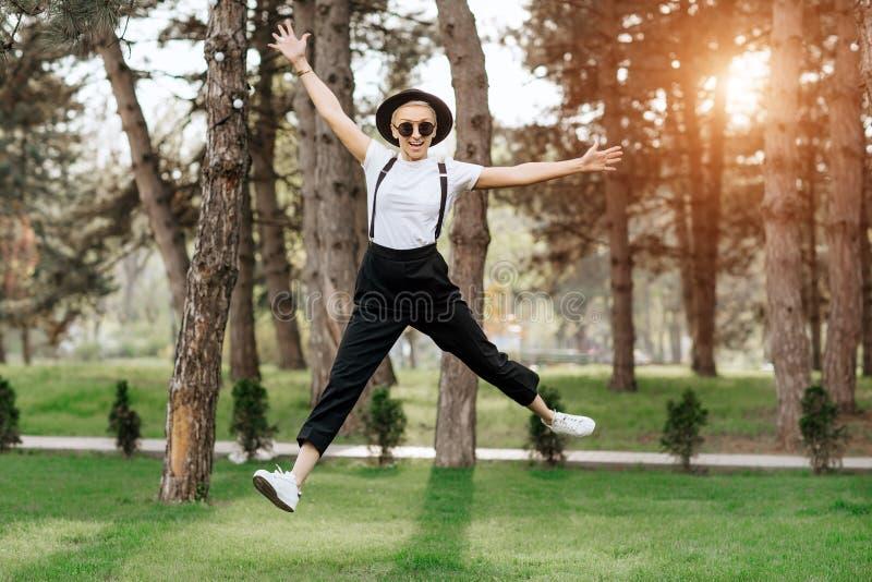 Har den unga kvinnan för den attraktiva moderiktiga lyckliga hipsteren i hatt och solglasögon gyckel i parkera på solnedgången sv arkivfoto