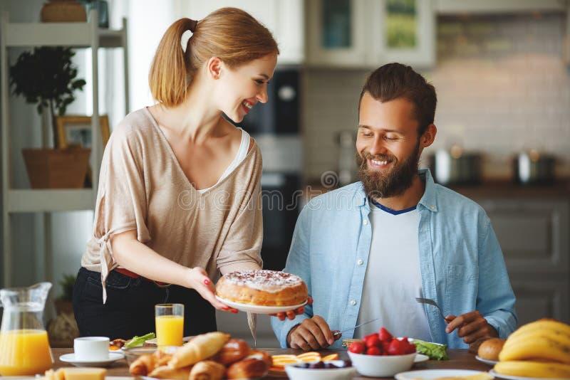 Har lyckliga par för familj frukosten i kök i morgon royaltyfri foto