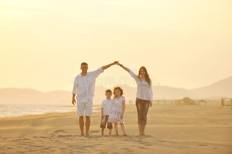 har roligt lyckligt för strandfamilj solnedgångbarn arkivbilder