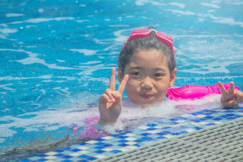 Har tycker om den asiatiska gulliga lilla flickan f?r lycka rolig k?nsla och i simbass?ng royaltyfri foto