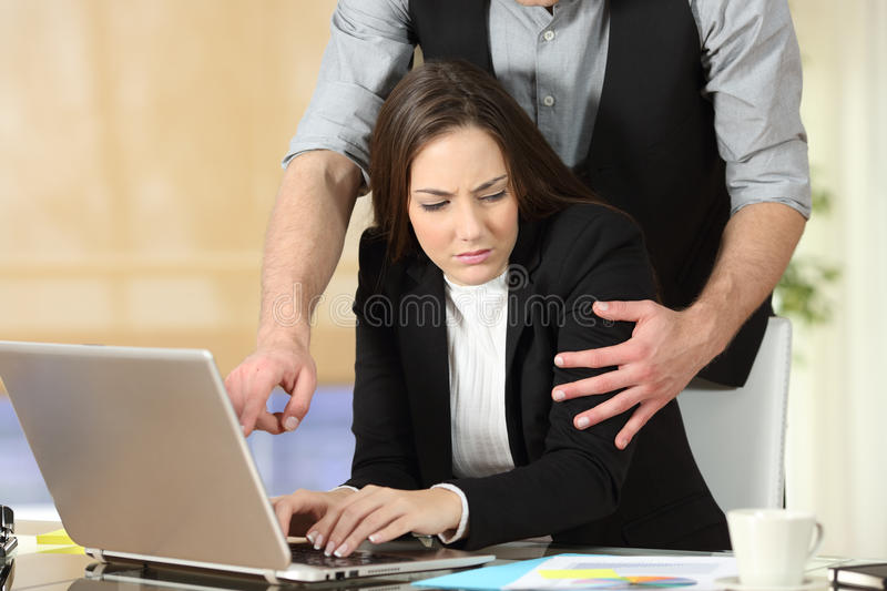 Harassment with a boss touching to his secretary. Harassment with a boss touching the arm to his secretary who is sitting in his workplace at office stock photo