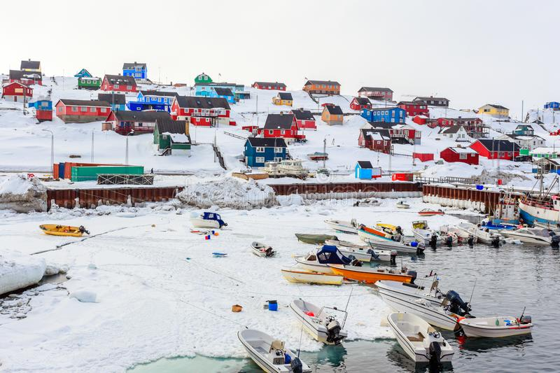 Harbor area with motorboats and colorful inuit houses in backgroung, Aasiaat city. Greenland architecture arctic beauty buildings built climate cold colored stock images