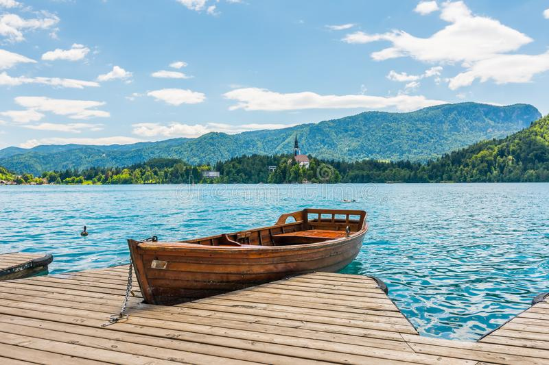 Harbor and boat on the Bled lake, Slovenia. Wooden boats on the pure blue water. Summer day near the Alps and forest royalty free stock image