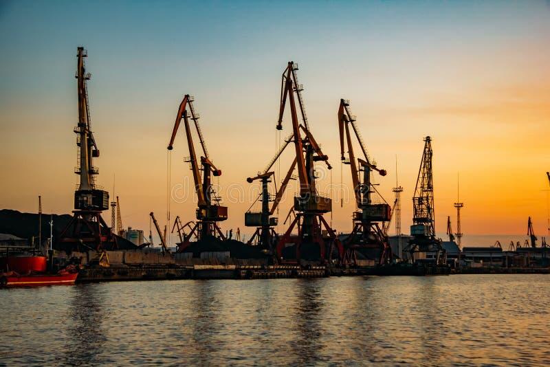 Harbor cargo cranes on sunset sky background.  stock photo