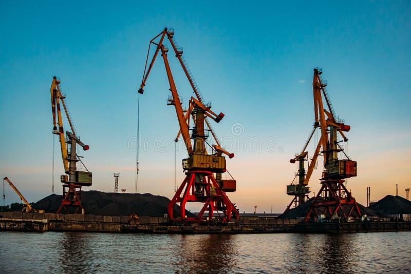 Harbor cargo cranes on sunset sky background.  royalty free stock photography