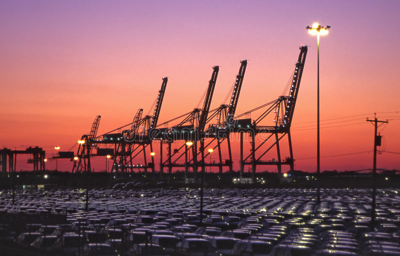 Harbor cranes and imported autos. Cranes located in the port of bayonne n.j. usa.at sunset.rows of imported autos in foreground royalty free stock images