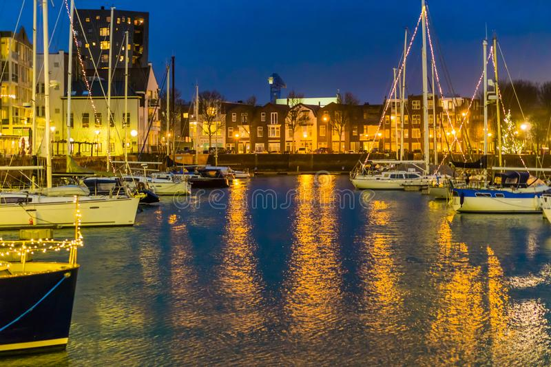 The harbor of Vlissingen at night, decorated boats with lights, lighted city buildings, popular city in zeeland, the Netherlands royalty free stock photos