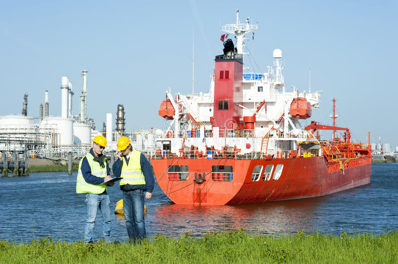 Harbor Workers. Two harbor workers at a petrochemical refinery harbor hard hats and safety vests discussing docking schedules stock photos