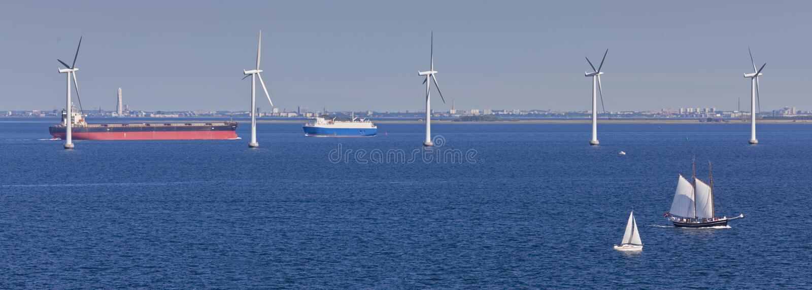Sailing ships, windmills and tankers stock photography